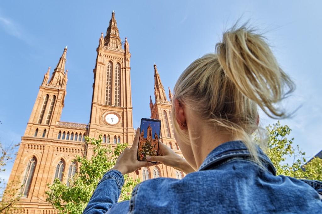 Blonde Frau macht mit ihrem Handy ein Bild von der Markt Kirche in Wiesbaden